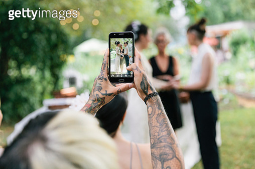 Tattoo woman using smartphone to take photo at wedding Ceremony - gettyimageskorea