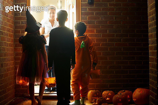 Rear view of three children wearing halloween costumes trick or treating - gettyimageskorea