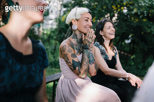 Tattooed wedding guest clasping her hands together as lesbian couple gets married. - gettyimageskorea