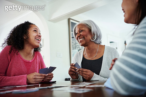 Smiling grandmother playing cards with family at home - gettyimageskorea