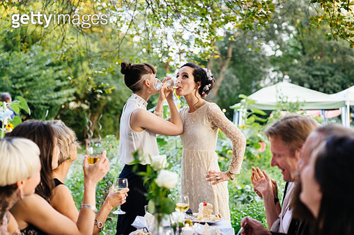 Newlywed young lesbian couple drinking together and celebrate their marriage with family and friends - gettyimageskorea