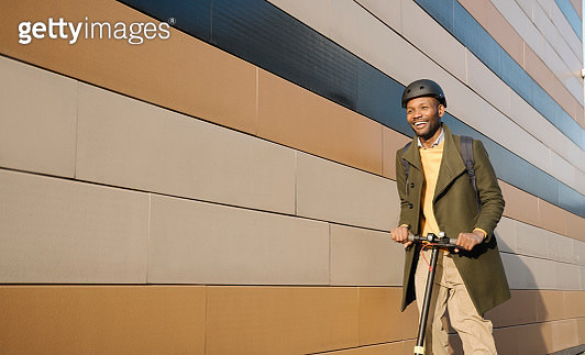 Happy man with helmet and scooter passing a building - gettyimageskorea