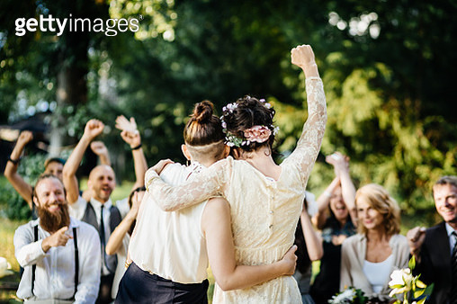Young lesbian couple celebrating their marriage in front of their friends. The wedding ceremony is outdoors - gettyimageskorea