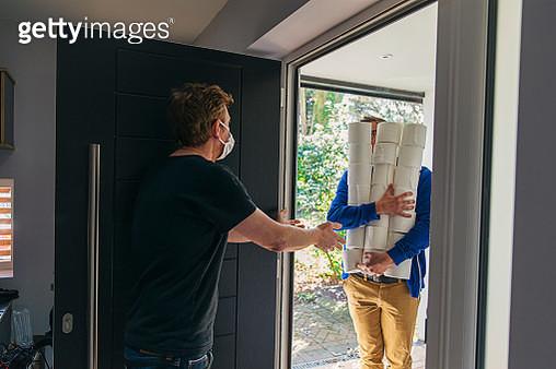 Man delivering huge pile of toilet rolls to customer in mask - gettyimageskorea