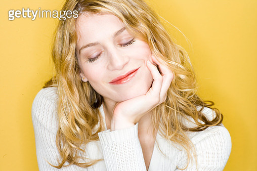Smiling woman resting chin in hand - gettyimageskorea