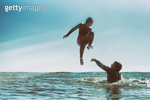 Father throwing son in the ocean - gettyimageskorea