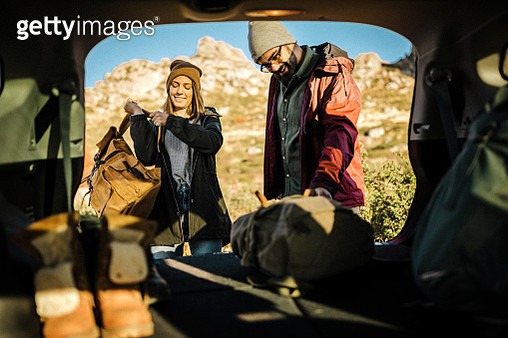 Couple taking backpack out of car trunk in nature - gettyimageskorea