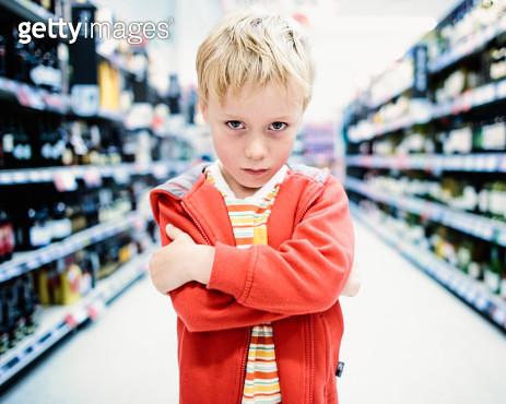 Close-up of boy standing in supermarket. - gettyimageskorea