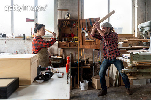Playful craftswoman and craftsman fighting in their workshop - gettyimageskorea