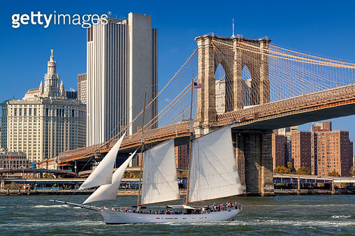 Schooner Sailing in East River and New York City Skyline with Brooklyn Bridge and Manhattan Municipal Building, NY, USA. - gettyimageskorea