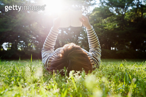 woman lying down on grass and reading a book. - gettyimageskorea