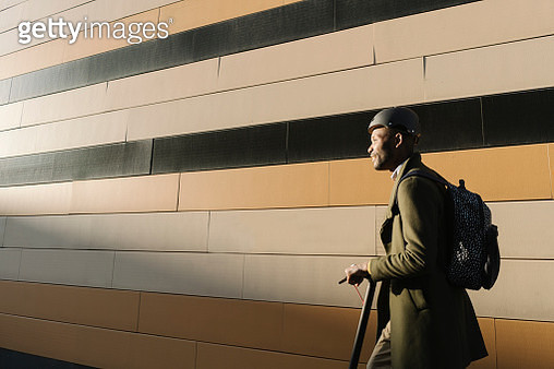 Stylish man with helmet and scooter at a building - gettyimageskorea