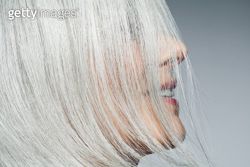 Grey haired woman profile with hair covering face. - gettyimageskorea