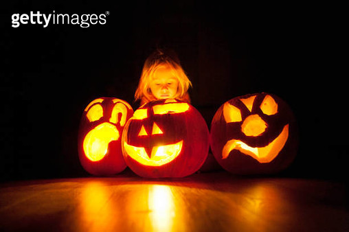 Girl (8-9) sitting next to Halloween pumpkins - gettyimageskorea