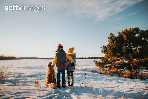 Boy and girl with their dog in a snowy field, United States - gettyimageskorea