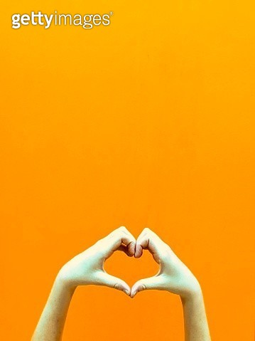 Heart with hands against a bright orange background - gettyimageskorea