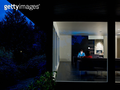 Husband and wife couple sitting in home at night - gettyimageskorea
