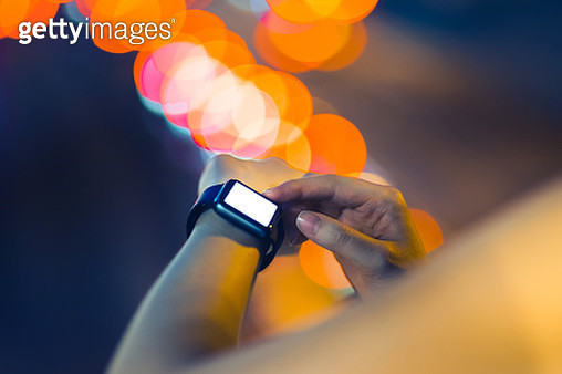 Human hands using smart watch outdoors at night - gettyimageskorea