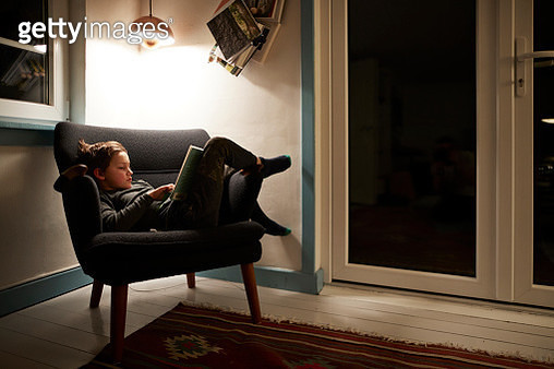Boy reading book under lamp in armchair at night - gettyimageskorea