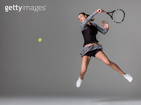 Full length of young woman playing tennis jumping in the air as she hit a forehand and is following through, tennis ball also in the photo, against gray background in studio - gettyimageskorea