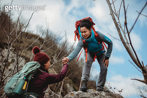 Woman giving a helping hand to her friend on mountain climbing - gettyimageskorea