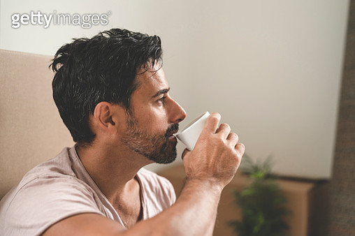 Man drinking coffee while moving into a new house - gettyimageskorea