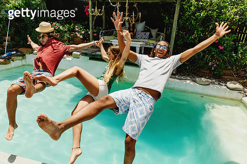 Three fully clothed friends falling backwards into pool - gettyimageskorea