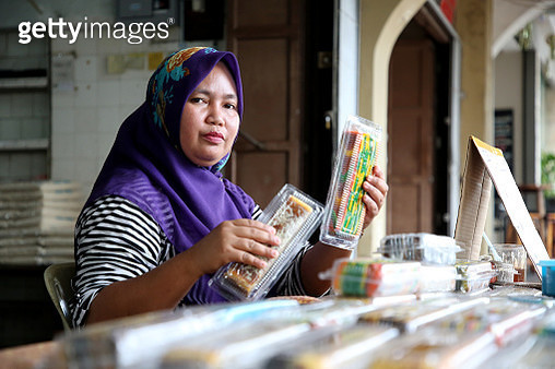 A female adult is feeling cheerful at her business stall selling famous 'kueh lapis' (traditional local colourful layer cake). - gettyimageskorea