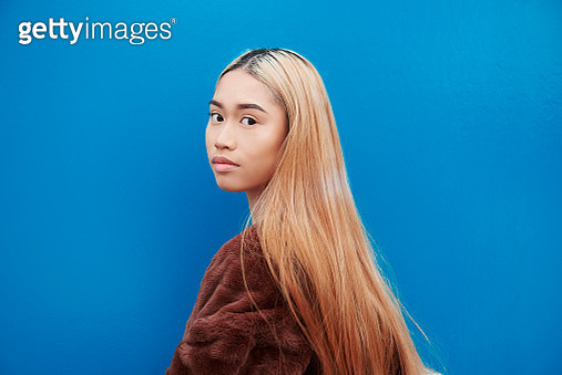 Young woman looking over shoulder to camera. - gettyimageskorea