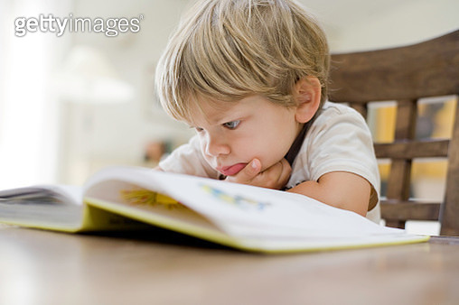 Boy reading book at table. - gettyimageskorea