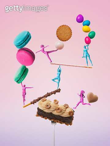 Girls figures taking a balance while exercising with sweets - gettyimageskorea