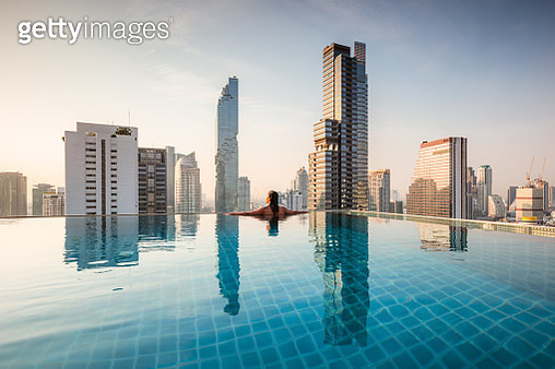 Beautiful woman in an infinity pool overlooking the skyline of Bangkok, Thailand - gettyimageskorea