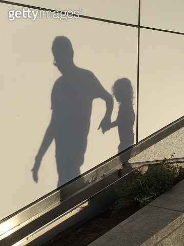 Brooklyn, NYC - October 14, 2017: The shadows on a wall surface of a father and daughter  on an outdoor staircase  in a public park with the man gently supporting the girl at the top of the steps on a bright sunny afternoon. - gettyimageskorea