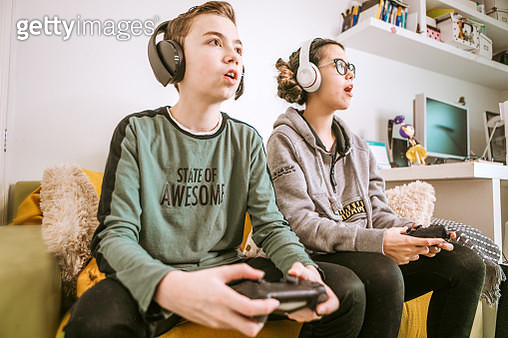 sibling competitive playing video games on tv at home - gettyimageskorea