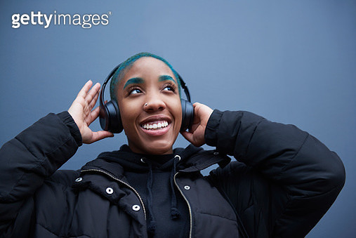 Young woman holding onto headphones smiling. - gettyimageskorea