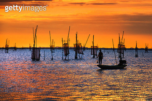 Fisherman on boat over the lake with sunset - gettyimageskorea