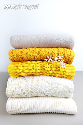 Stack of trend Yellow Orange Woolen Knitted Sweaters close-up, texture, background. - gettyimageskorea