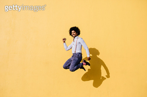 Smiling man jumping in the air in front of yellow wall - gettyimageskorea