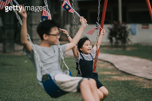 an asian chinedse brother and sister sibling holding malaysia national flag and swinging at children playground smiling enjoying bonding time - gettyimageskorea