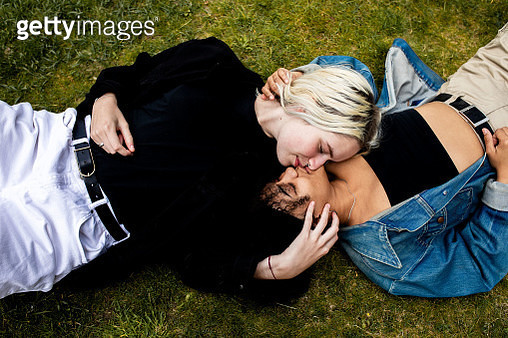 A lesbian couple lying in the grass, kissing - gettyimageskorea