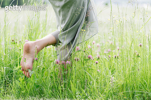 Frau läuft barfuss durch grünes hohes Gras - gettyimageskorea