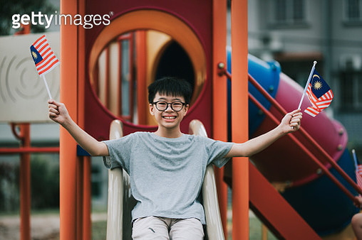 an asian chinese young boy holding malaysia national flag in children playground - gettyimageskorea