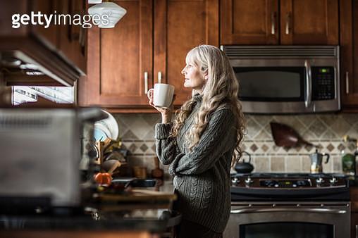 Portrait of woman (60yrs) having coffee in kitchen - gettyimageskorea