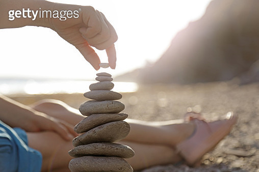 Woman stacking stones on beach - gettyimageskorea
