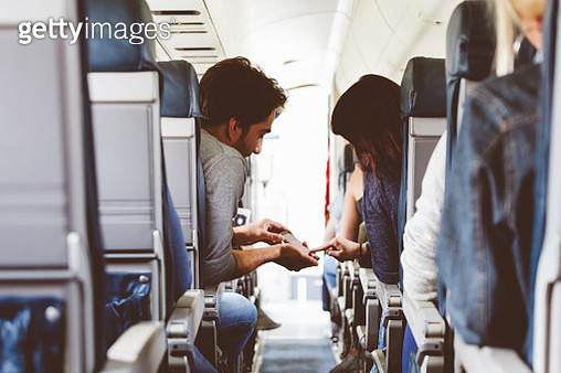 Young couple using mobile phone in the flight - gettyimageskorea