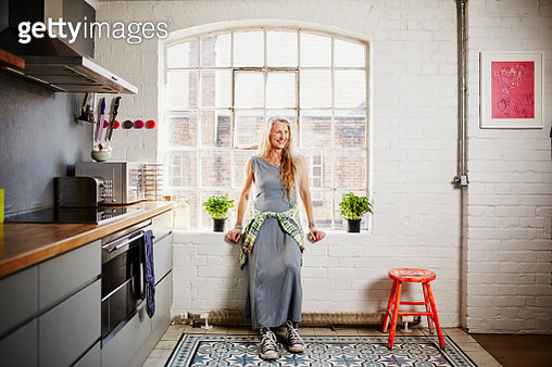 A cool older woman stands by the window in her modern kitchen giving a big smile - gettyimageskorea