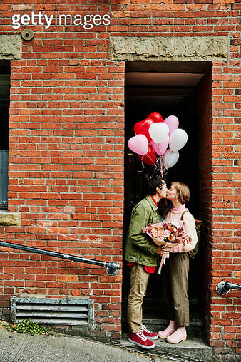 Couple kissing in doorway while on Valentines Day date - gettyimageskorea