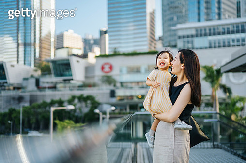 Young Asian mother and cute little daughter smiling joyfully over the urban terrace in downtown district against modern skyscrapers - gettyimageskorea