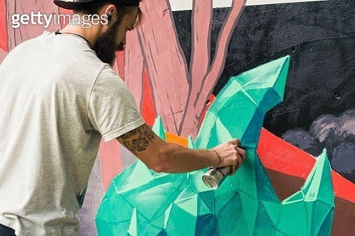 Street Artist Painting Graffiti With Aerosol Can On Wall - gettyimageskorea