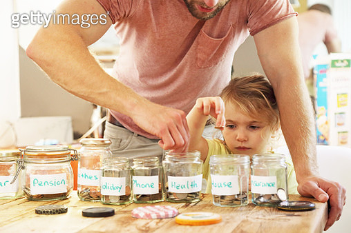 Young girl and father putting money into savings jars - gettyimageskorea